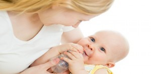 mother feeding from bottle her adorable baby boy